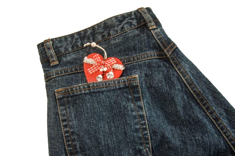 Jeans med röd julhjärta i fack Isolerat över vit royaltyfria foton