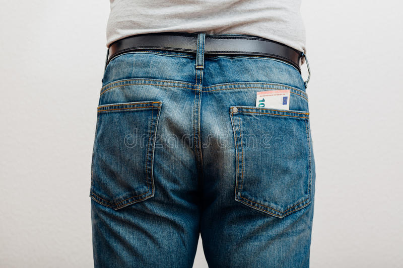 Jeans with money in pocket. Closeup to back of man, jeans with money in pocket, people studio indoors shot stock photography