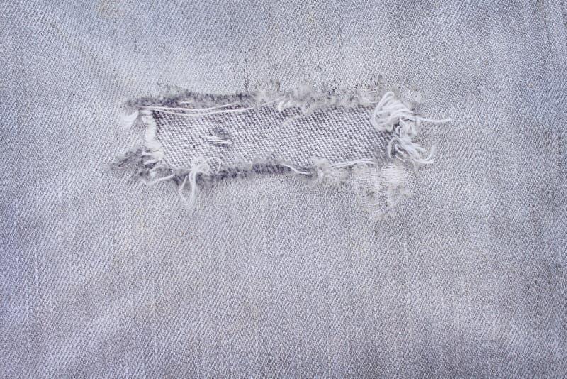 Jeans noirs légers avec la texture déchirée de modèles pour le fond, le trou et les fils blancs détruits sur le denim photographie stock