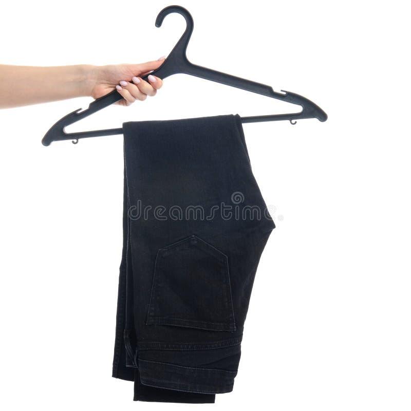 Jeans noirs sur un cintre à disposition images stock