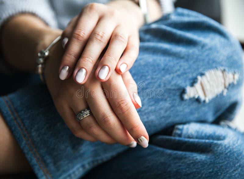 Jeans och en härlig manikyr kvinna för stil för blåtiraframsidamode sexig arkivbilder