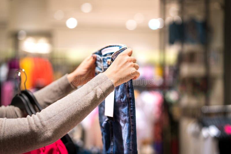 Jeans och shopping för kvinna hållande i modeklädlager royaltyfri bild