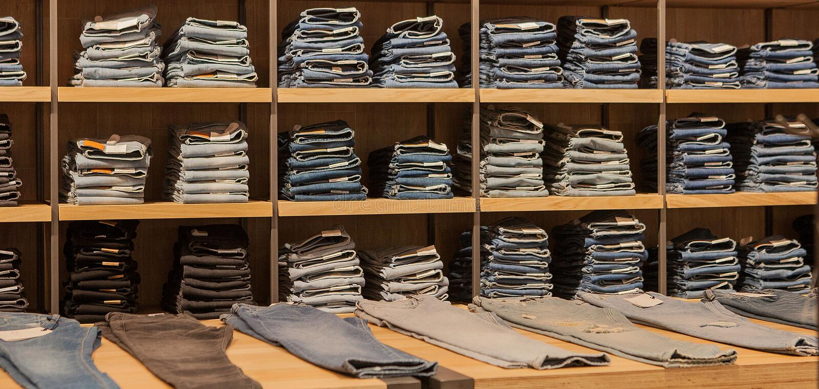 Jeans pants on the store shelf. Blue jeans denim Collection jeans stacked. Jeans hanging on the vests in the fashion store. Showcase, sale, shopping stock image