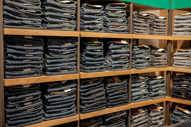 Jeans pants on the store shelf. Blue jeans denim Collection jeans stacked.  stock photo