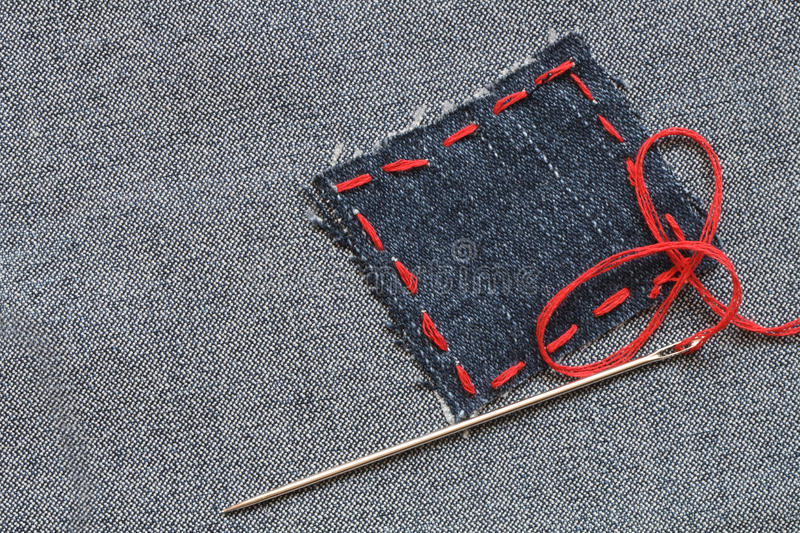 Jeans Patch. Needle and patch with red thread attached on jeans textured royalty free stock photos