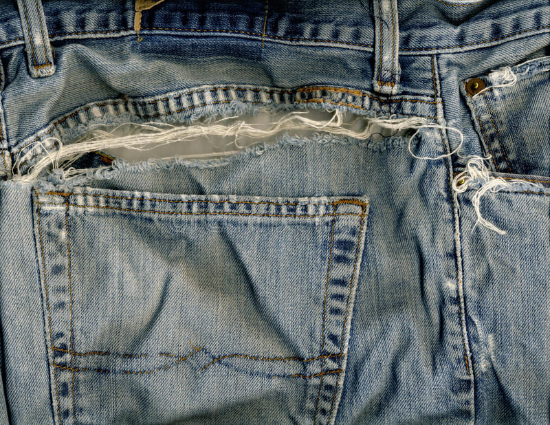 Jeans pocket & rip. Blue jeans denim back pocket and waistband, with a large rip stock photo