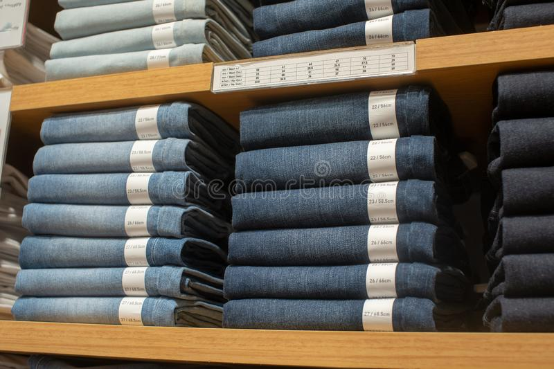 Jeans put on sale in shop, The seller in a clothing store. royalty free stock images
