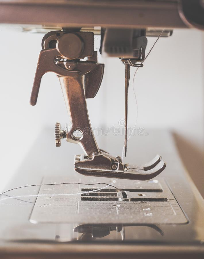 Jeans rammendanti su una macchina per cucire fotografia stock