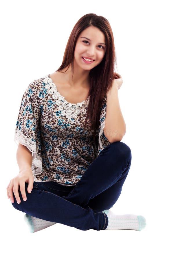 Jeans s'usants de sourire de jolie femme se reposant sur l'étage photo libre de droits