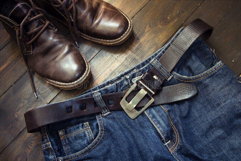 Jeans schnallen und die Schuhe um, die auf Holz eingestellt werden stockbild