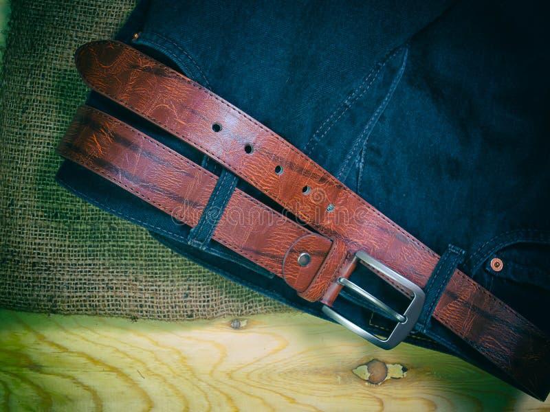 Jeans schwärzen, schnallen um, setzen an Sackleinen lizenzfreie stockfotografie