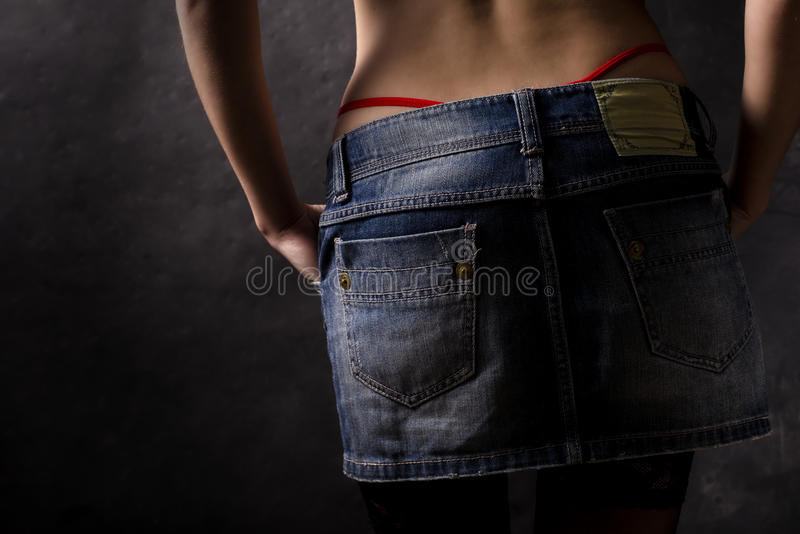 Jeans skirt closeup. From back with red strigs out royalty free stock photo