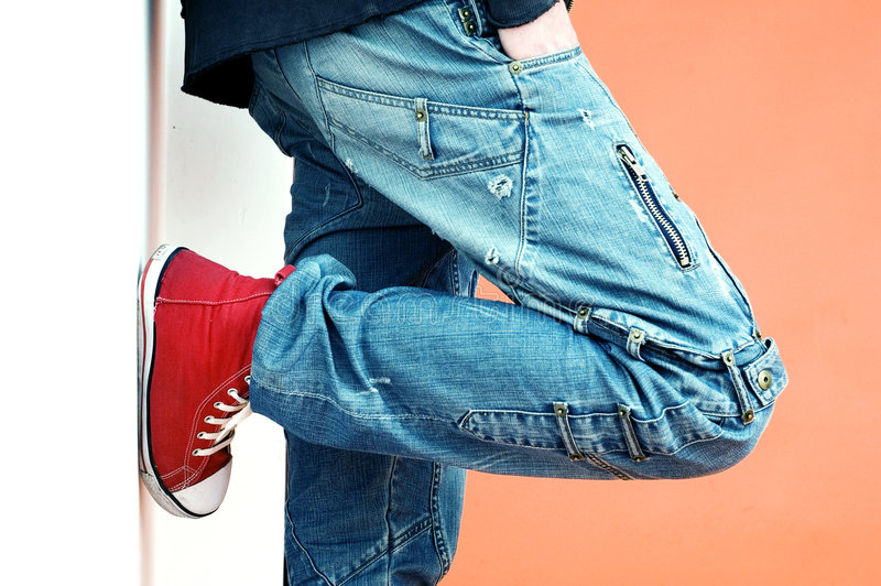 Jeans and Sneakers. A close up shot of a man wearing a pair of jeans and leaning against a wall. He's wearing red canvas sneakers