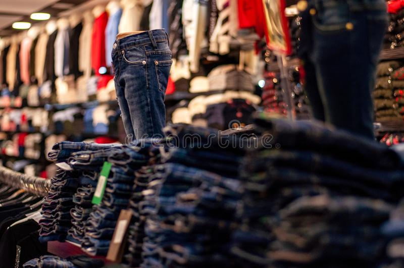 Jeans are stacked in piles in a store. Jeans are stacked on a shelf. Size range. stock photos