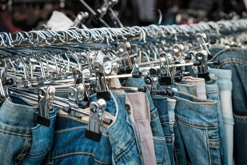 Jeans sui ganci, deposito della seconda mano, primo piano dei pantaloni immagini stock libere da diritti