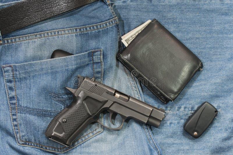 Jeans, svartläderBi-veck plånbok, handeldvapen och en biltangent royaltyfria foton