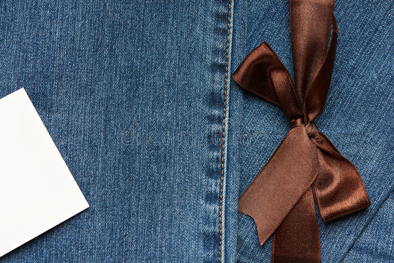 Jeans texture with brown ribbon. Blue Jeans texture with brown ribbon and white empty tag label royalty free stock photography