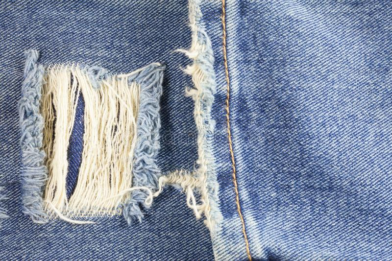 Jeans torn denim texture. Abstract, background, blue, canvas, casual, closeup, cloth, clothes, clothing, design, detail, fabric, fashion, fiber, grunge, hole stock image