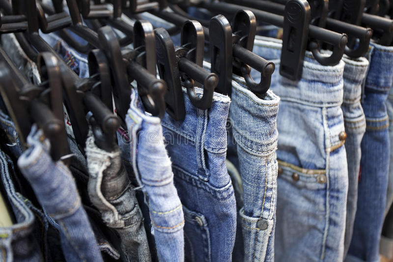 Jeans and trousers on hangers stock photography