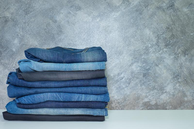 Jeans trousers stacked, Clothing, Denim on white table with cement background. Beauty and fashion stock photo