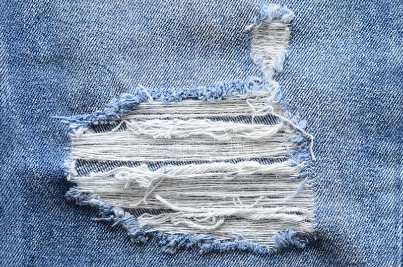 Jeans in wash blue with rip. Denim background, texture. Ripped d. Estructed detail, close up royalty free stock photo