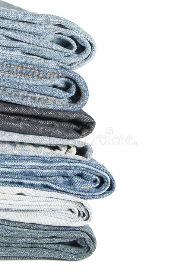 Jeans on a white background. Flat pile of jeans on a white background royalty free stock photo