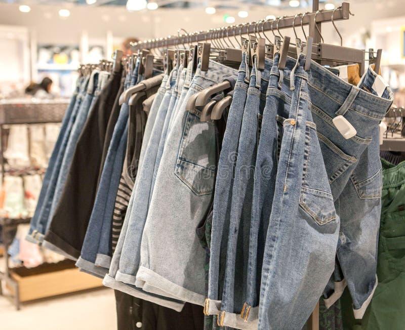 Jeansborrels op de opslagplank Modieuze kleren op de planken in de opslag Jeans die op de vesten in de manieropslag hangen royalty-vrije stock afbeeldingen