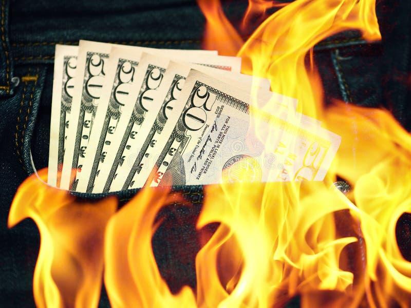 Jeansbyxan stoppa i fickan 50 amerikanska dollar och flammor fotografering för bildbyråer