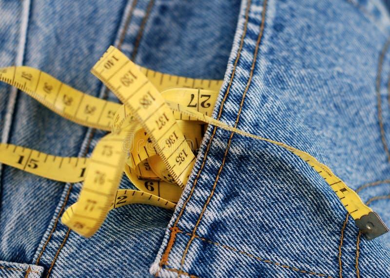 Jeansdenim en gele maatregelenband stock fotografie