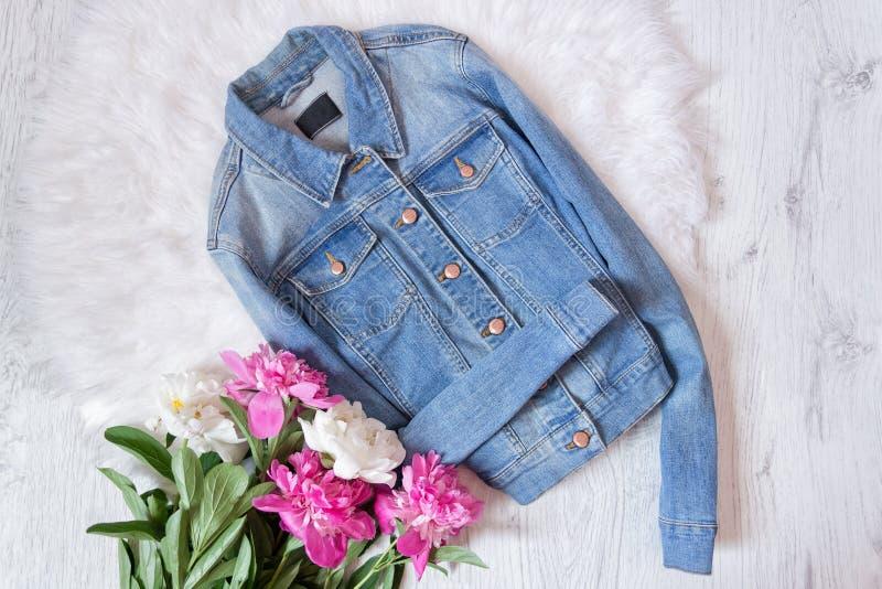 Jeansjasje en een boeket van pioenen Modieus concept, wit bont op de achtergrond royalty-vrije stock foto's