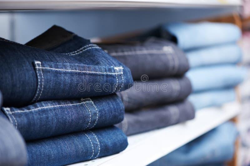 Jeanskleidung auf Regal im System stockbilder