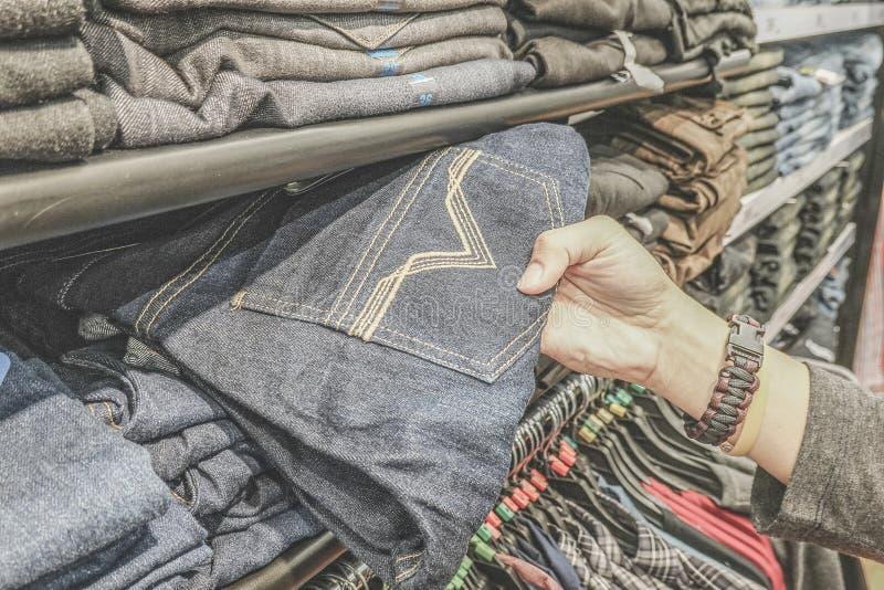 Jeansspeichereinkaufen Regal mit neuen Blue Jeans im Speicher Mannhandkontrolle einige Jeans und irgendein Einzelteil wählen stockfotografie