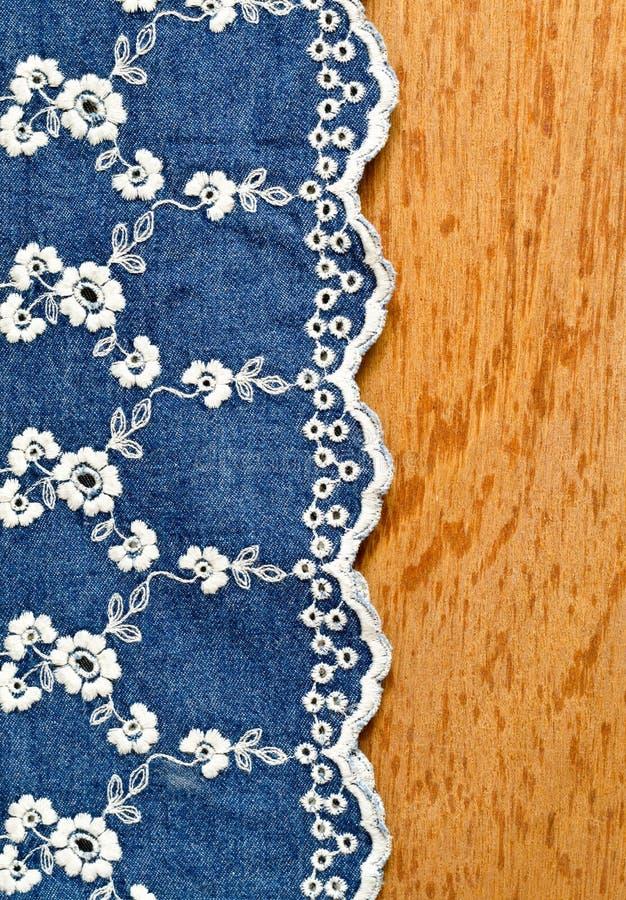 Jeansstof met wit die bloemborduurwerk over triplex wordt gelegd royalty-vrije stock foto