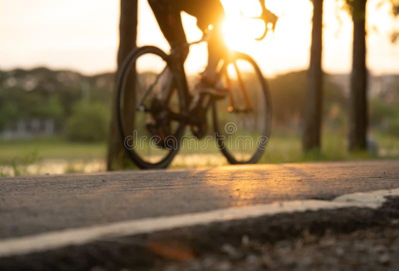 Jechać na rowerze przy lato zmierzchem na drodze w miasto parku Cyklu zbliżenia wh zdjęcia stock