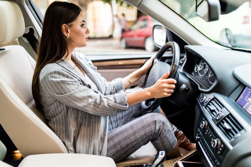 Jechać wokoło miasta Młoda atrakcyjna kobieta uśmiechnięta i patrzeje prosty podczas gdy jadący samochód obraz stock