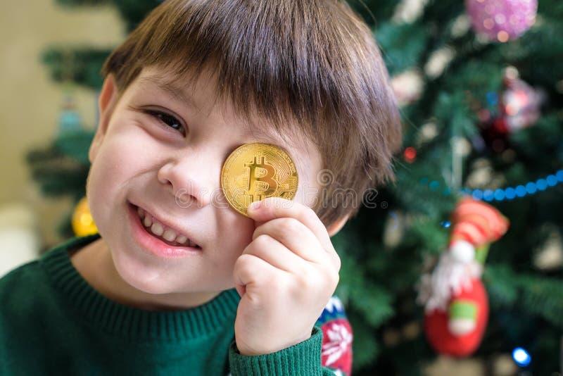 Jeden Bitcoin w ręce młoda chłopiec Pojęcie Crypto cyfrowy złoto fotografia royalty free