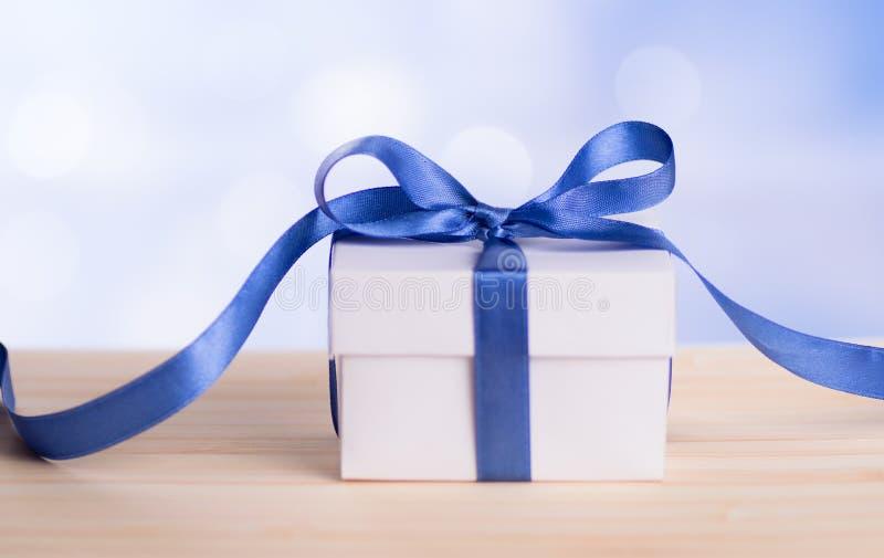 Jeden Bożenarodzeniowy prezenta pudełko z błękitnego faborku łękiem i bokeh tłem obrazy stock