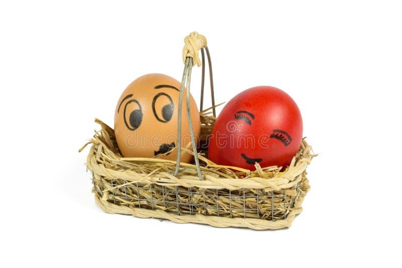 Jeden Brown i Jeden Czerwony jajko z Śmieszną twarzą w Łozinowym koszu Odizolowywającym na bielu zdjęcia stock