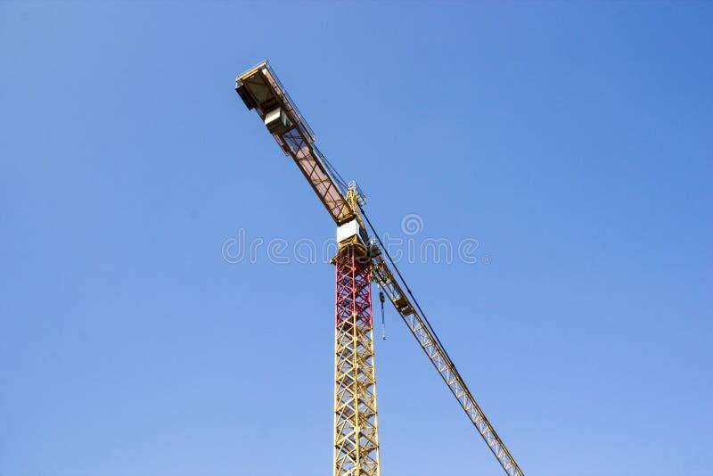 Jeden budowy duzi żółci żurawie na niebieskiego nieba tle zdjęcie stock