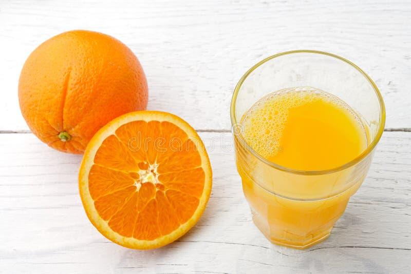 Jeden cały obok szkła odizolowywającego na bielu świeży sok pomarańczowy i połówka pomarańcze malowaliśmy drewno zdjęcia royalty free