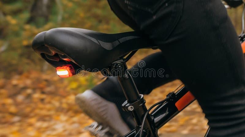 Jeden caucasian dzieci przejażdżek roweru droga w jesień parku Mała dziewczynka jedzie czarnego pomarańczowego cykl w lasowym dzi obrazy stock