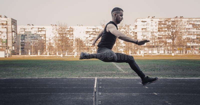 Jeden caucasian samiec w skoku nad barierą biegać na stadium Zawody atletyczni biegacz w sporta mundurze w locie energiczny obraz royalty free