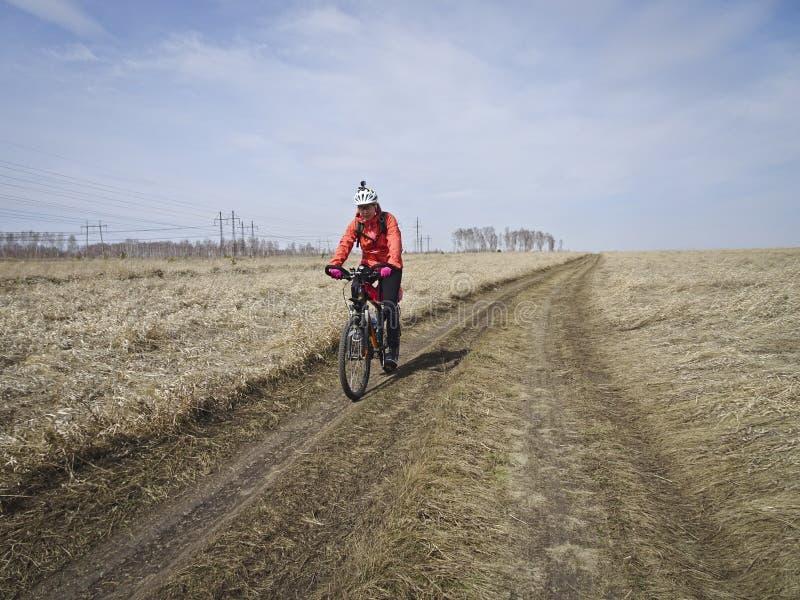 Jeden cyklista w jaskrawym odziewa przejażdżki na śródpolnej drodze wśród niekończący się stepów w wiośnie obrazy royalty free