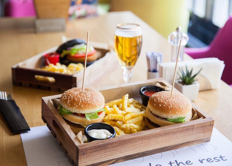 Jeden czarny barwiony i dwa normalny mały podlewanie, wyśmienicie hamburgery na drewnianej tacy słuzyć z czerwonym ketchupu kumbe fotografia stock