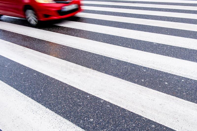 Jeden czerwień, post, niebezpieczny zamazany samochód na crosswalk, żadny ludzie, mokry asfalt, no opróżnia przestrzeni obrazy royalty free