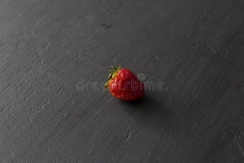 Jeden czerwona pi?kna truskawka w g?r? na czarnym zmroku betonu tle, minimalista Boczny widok, kopii przestrze? dla tw?j teksta M fotografia stock