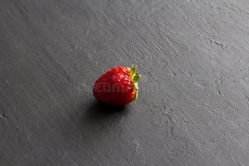 Jeden czerwona pi?kna truskawka w g?r? na czarnym zmroku betonu tle, minimalista Boczny widok, kopii przestrze? dla tw?j teksta M fotografia royalty free