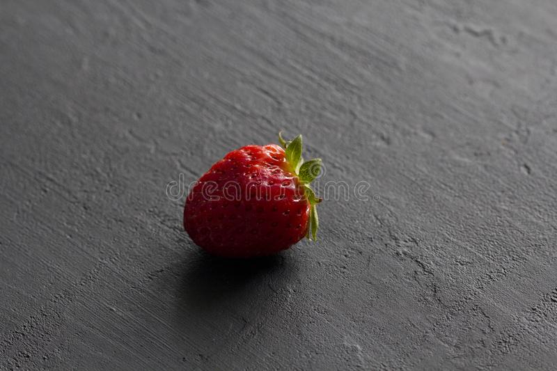 Jeden czerwona pi?kna truskawka w g?r? na czarnym zmroku betonu tle, minimalista Boczny widok, kopii przestrze? dla tw?j teksta M obraz stock