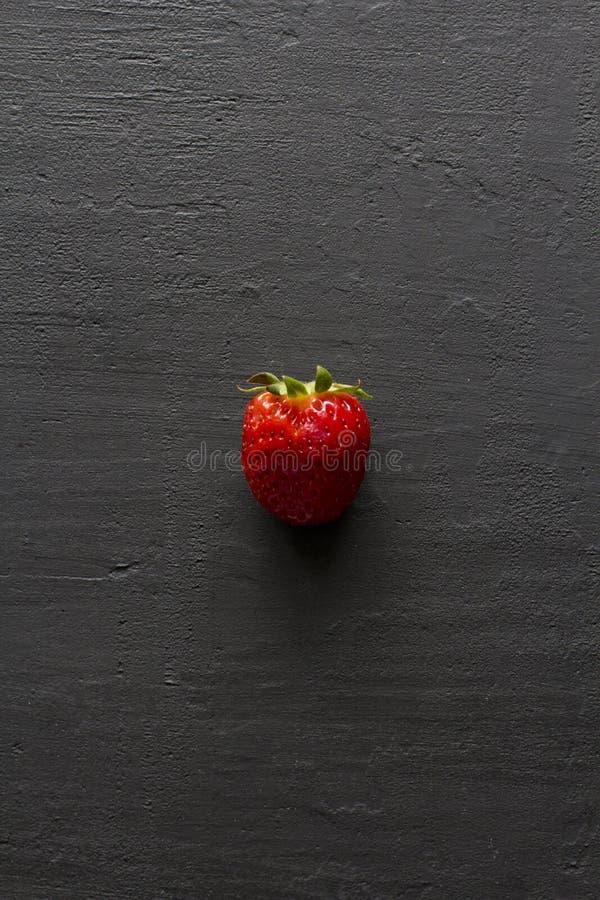 Jeden czerwona pi?kna truskawka w g?r? na czarnym zmroku betonu tle, minimalista Mieszkanie Lay, Odg?rny widok, kopii przestrze?  zdjęcie royalty free