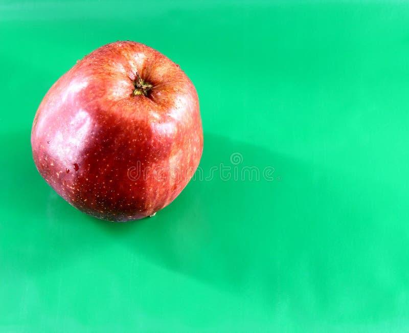 Jeden czerwony Jabłczany świeży z wodnymi kroplami na zielonym tle fotografia royalty free